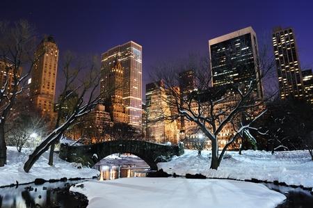 뉴욕시 눈, 다리와 함께 겨울 맨하탄 중앙 공원 파노라마; 황혼의 호수와 고층 빌딩을 동결.