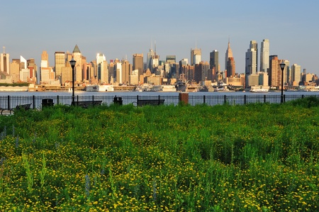 weehawken: New York City Manhattan midtown skyline view from New Jersey Hudson River waterfront park with green lawn at sunset.