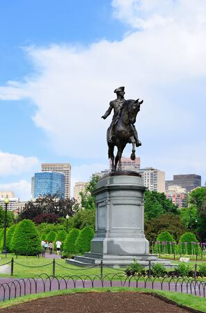 the common: George Washington statue as the famous landmark in Boston Common Park with city skyline and skyscrapers.