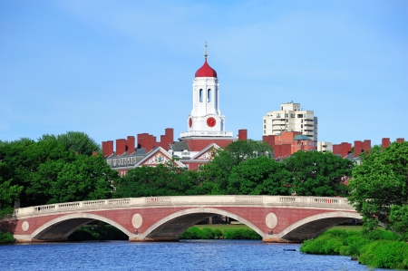 harvard: John W. Weeks Bridge and clock tower over Charles River in Harvard University campus in Boston with trees and blue sky.