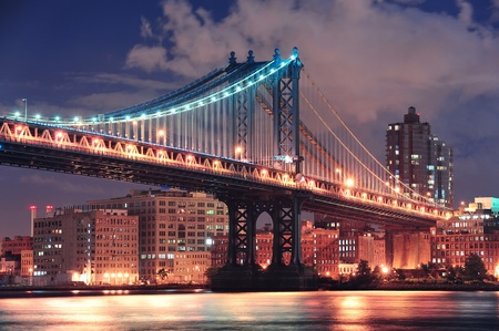east river: Manhattan Bridge closeup over East River at night in New York City Manhattan with lights and reflections.