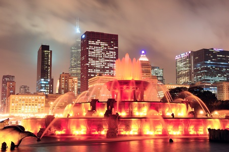 Chicago skyline with skyscrapers and Buckingham fountain in Grant Park at night lit by colorful lights. Stock Photo