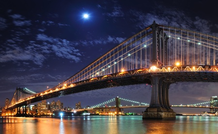 Brooklyn Bridge and Manhattan Bridge over East River at night with moon in New York City Manhattan with lights and reflections. Stock Photo