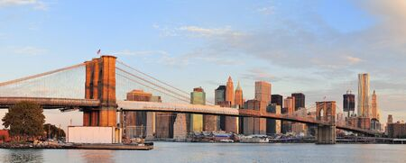 Brooklyn Bridge with lower Manhattan skyline panorama in the morning with colorful cloud over East River in New York City photo