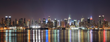 New York City Manhattan midtown skyline at night with lights reflection over Hudson River viewed from New Jersey Weehawken waterfront. Stock Photo