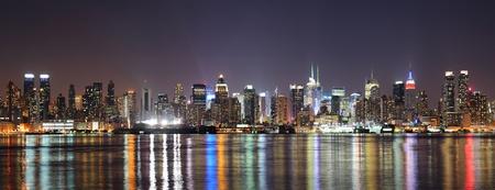 new york times square: Nueva York Midtown Manhattan horizonte en la noche con la reflexi�n sobre las luces vistas del r�o Hudson de Nueva Jersey Weehawken l�nea de costa.