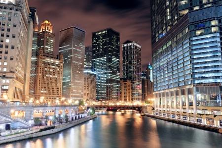 Chicago River Walk met stedelijke wolkenkrabbers verlicht met lichten en water reflectie in de nacht.