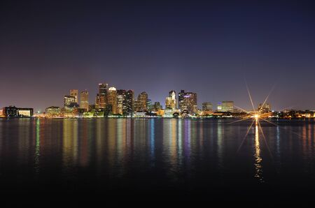 Boston downtown with urban city skyline at night with skyscrapers illuminated over sea.