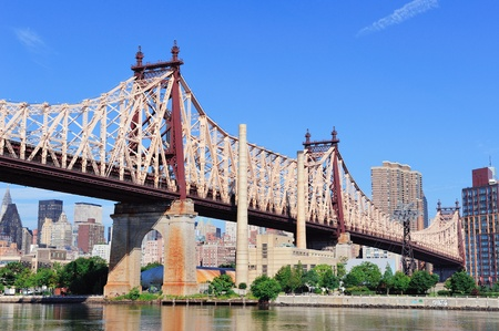 Queensborough Bridge in Midtown Manhattan with New York City skyline over East River as the famous landmarks viewed from Brooklyn. photo