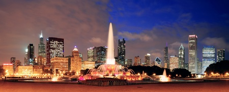Chicago skyline panorama with skyscrapers and Buckingham fountain in Grant Park at night lit by colorful lights. Editorial