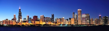 Chicago city downtown urban skyline panorama at dusk with skyscrapers over Lake Michigan with clear blue sky.