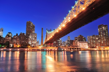 Queensboro Bridge over New York City East River at sunset with river reflections and midtown Manhattan skyline illuminated.  photo