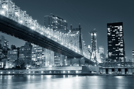 Queensboro Bridge over New York City East River black and white at night with river reflections and midtown Manhattan skyline illuminated.  photo