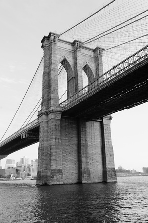 Brooklyn Bridge black and white over East River viewed from New York City Lower Manhattan waterfront.