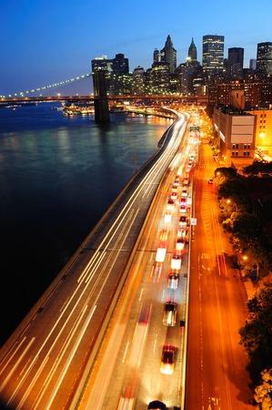 New York City Manhattan Skyline der Innenstadt Luftbild bei Dämmerung beleuchtet Wolkenkratzer mit über East River mit Reflexionen.