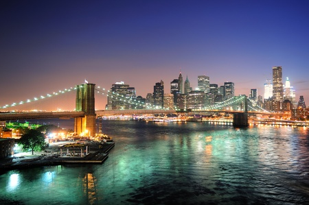 New York City skyline di downtown Manhattan veduta aerea al crepuscolo con grattacieli illuminati su East River con riflessi.