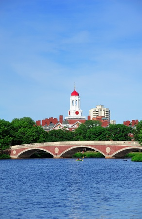 ivy league: John W. Weeks Bridge and clock tower over Charles River in Harvard University campus in Boston with trees, boat and blue sky. Stock Photo