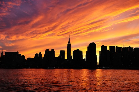 red sunset: New York City Manhattan midtown silhouette panorama at sunset with skyscrapers and colorful sky over east river Stock Photo