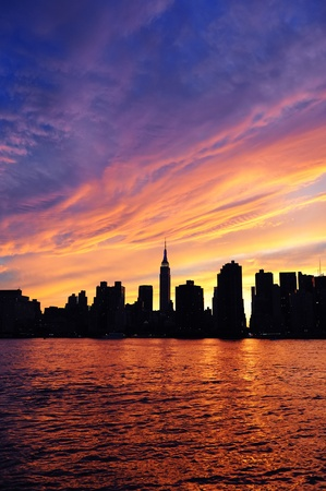 New York City Manhattan midtown silhouette panorama at sunset with skyscrapers and colorful sky over east river Stock Photo