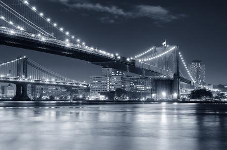 Brooklyn Bridge über den East River in der Nacht in Schwarz und Weiß in New York City Manhattan mit Lichtern und Reflexen.