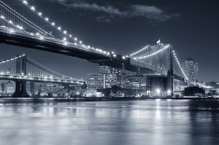 skyline nyc: El puente de Brooklyn sobre el East River en la noche en blanco y negro en Nueva York Manhattan con luces y reflejos.