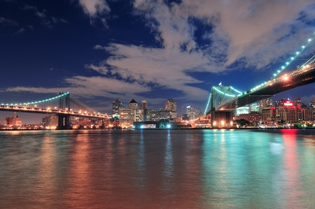 Manhattan Bridge and Brooklyn Bridge panorama over East River at night in New York City Manhattan with lights and reflections. photo