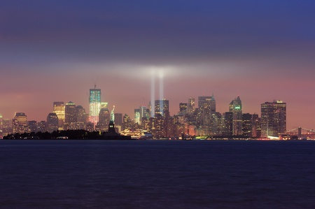 september 11: New York City Manhattan downtown skyline at night with statue of liberty and light beams in memory of September 11 viewed from New Jersey waterfront.