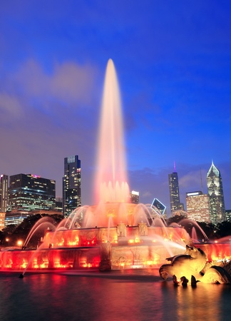 Chicago skyline with skyscrapers and Buckingham fountain in Grant Park at dusk lit by colorful lights. photo
