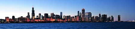 city panorama: Chicago city downtown urban skyline panorama at dusk with skyscrapers over Lake Michigan with clear blue sky.