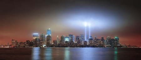 New York City Manhattan downtown skyline at night from Liberty Park with light beams in memory of September 11 viewed from New Jersey waterfront. photo