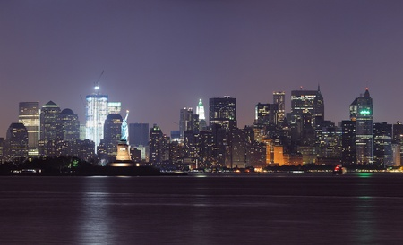 New York City lower Manhattan skyline at night with Statue of Liberty and urban city skyline over river panorama view. photo