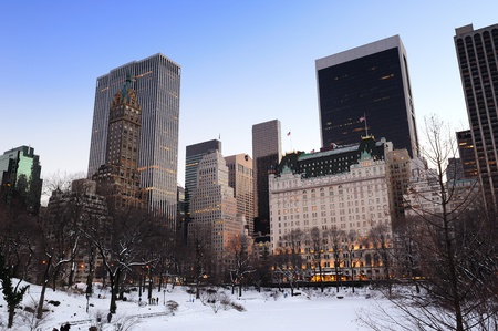 New York City Manhattan Central Park panorama in winter with snow, freezing lake and skyscrapers at dusk. photo