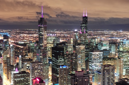 Chicago urban skyline panorama aerial view with skyscrapers and cloudy sky at dusk with lights. photo