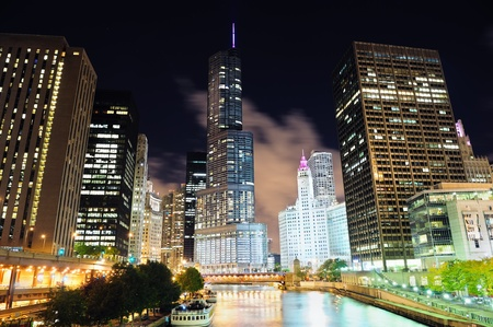 Chicago River Walk with urban skyscrapers illuminated with lights and water reflection at night.  photo