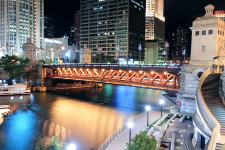 Chicago River Walk with urban skyscrapers and bridge illuminated with lights and water reflection at night.  photo