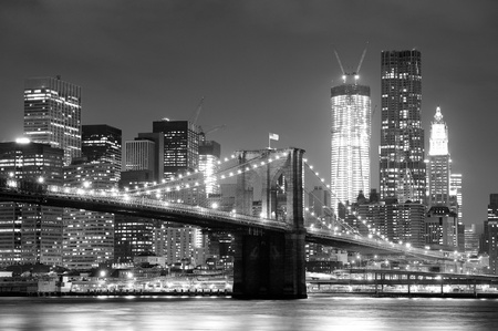 new york notte: New York City Brooklyn Bridge in bianco e nero con skyline del centro sull'East River.