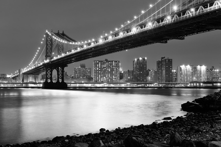 black and white: New York City Manhattan Bridge closeup black and white with downtown skyline over East River.