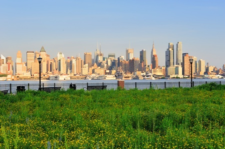 New York City Manhattan midtown skyline view from New Jersey Hudson River waterfront park with green lawn at sunset. photo