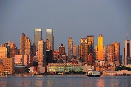 weehawken: New York City Manhattan sunset panorama with historical skyscrapers over Hudson River with beautiful red color sunshine reflection viewed from New Jersey Weehawken waterfront.