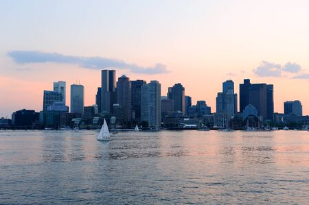 panoramic business: Boston downtown sunset skyline over river with skyscrapers and boat.