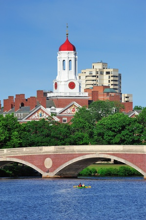 John W. Weeks Bridge and clock tower over Charles River in Harvard University campus in Boston with trees, boat and blue sky. photo