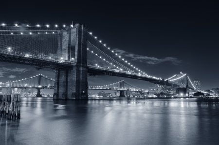 sky bridge: Brooklyn Bridge over East River at night in black and white in New York City Manhattan with lights and reflections.