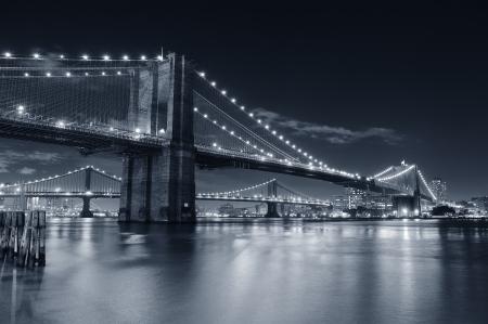 Ponte di Brooklyn sull'East fiume durante la notte in bianco e nero a New York City Manhattan con luci e riflessi.