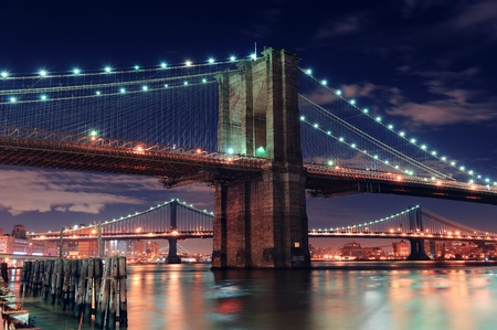 Brooklyn Bridge closeup over East River at night in New York City Manhattan with lights and reflections. photo