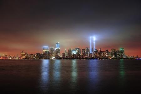 11 september: Ciudad de Nueva York el centro de Manhattan en la noche de Liberty Park con haces de luz en la memoria del 11 de septiembre visto desde muelles de Nueva Jersey.