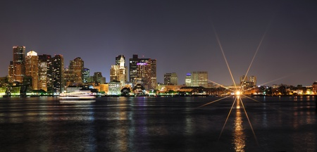 Boston downtown with urban city skyline at night with skyscrapers illuminated over sea. photo