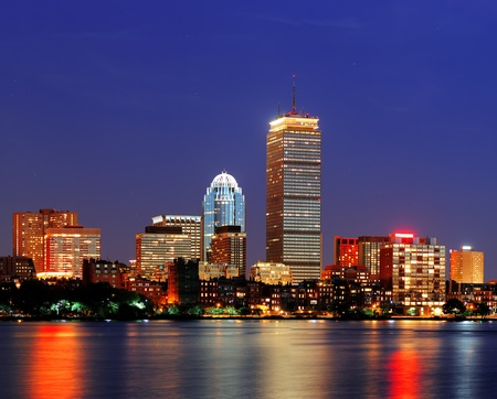 prudential: Boston city skyline at dusk with Prudential Tower and urban skyscrapers over Charles River with lights and reflections.