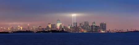 september 11: New York City Manhattan downtown skyline panorama at night with statue of liberty and light beams in memory of September 11 viewed from New Jersey waterfront.