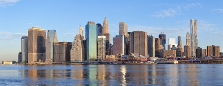 Lower Manhattan skyline panorama over East River with reflection and blue sky in New York City photo