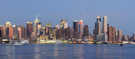 Hudson River waterfront view of New York City Manhattan after sunset with cityscape panorama and light reflection in tranquil blue tone. photo